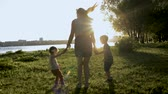 zoon : Silhouettes of mom with two children jumping in park Stockvideo