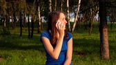 online : Young girl answers phone calling in the park. Smiling and happy