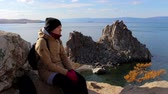coat : Girl sitting on a rock by the sea on a background of amazing landscape. Young woman looks into the distance, enjoying the beautiful scenery. Burhan, Olkhon Island, Lake Baikal, Siberia, Russia Stock Footage