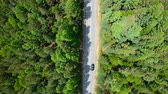 Aerial view of black car driving on road in forest. Slow