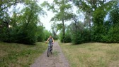 bisiklete binme : Cycling in the park. Girl riding a bike on a forest trail. Front view