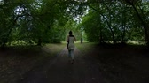joggers : Jogging in the park. Girl running along the forest path. Back view. Slow motion