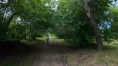 bisiklete binme : Cycling in the park. Girl riding a bike on a forest trail. Back view. Slow motion Stok Video