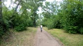 Cycling in the park. Girl riding a bike on a forest trail very quickly. Time lapse. Back view