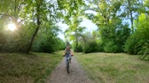 フロント : Cycling in the park. Girl riding a bike on a forest trail. Front view