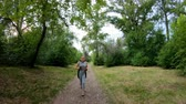 joggers : Jogging in the park. Girl running along the forest path. Front view. Slow motion
