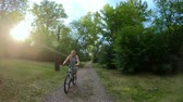 Cycling in the park. Girl riding a bike on a forest trail. Front view. Slow motion