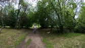 human back : Cycling in the park. Girl riding a bike on a forest trail. Back view. Slow motion Stock Footage