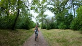 bisiklete binme : Cycling in the park. Girl riding a bike on a forest trail. Front view. Slow motion