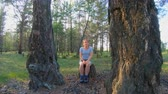 toco : Portrait of a girl sitting on a stump between two large trees in the woods