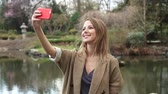 Young redhead woman making a selfie with mobile phone