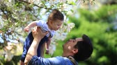 father and child have a leisure in springtime flowering garden in sunny day.