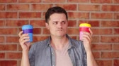 herbata : Footage of a young man holding a colored cup of drink on brick wall backgorund