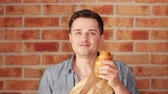 parede de tijolos : Young holding a country bread on blick wall background Stock Footage