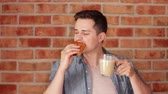 пекарня : Young eating a bun and drinking a coffee on blick wall background Стоковые видеозаписи
