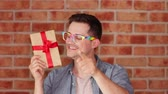коробка подарка : Footage of a young man holding gift box on brick wall backgorund