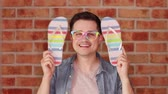 sandálias : Footage of a young man holding a colored flip flops shoes and preparing for summer vacation Stock Footage
