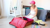 inpakken : Young girl prepearing for vacation. Pack up clothes in suitcase at home.