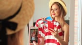 blogger : Young girl dressing up near a mirror. Choosing a clothes for vacation and making a selfie