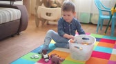 hipopótamo : The little boy sits on the floor and plays with various animals