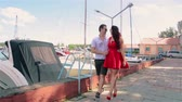 movable : Girl in red dress walking down the pier with her boyfriend