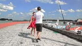 movable : Young beautiful girl goes barefoot on the pier with a young man