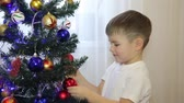 poczekalnia : A small child looks at the Christmas tree toys HD Wideo
