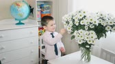 Little boy sniffs a huge bouquet of daisies HD 1080