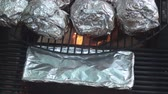 folyo : Cooking potatoes on the fire pits grill wrapped in aluminum foil.