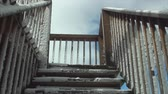 pegajoso : Stairs to the sky in time lapse. Wooden stairs covered in ice and snow. Houses porch and deck.