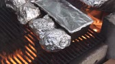 cooks : Cooking potatoes on the fire pits grill warped in aluminum foil. Stock Footage