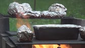 folyo : Cooking potatoes on the fire pits grill warped in aluminum foil 5.