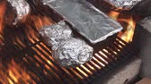 cooks : Cooking potatoes on the fire pits grill warped in aluminum foil 2.
