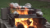 folyo : Cooking potatoes on the fire pits grill warped in aluminum foil 4.