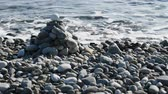 tomada : Entertainment for beachgoers. Cairn, cone is formed of pebbles on seashore, with waves always