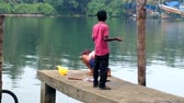 азиатский : India, Kerala - December 26, 2015:  entertainment of Indians 2. Two little boys to fish on homemade primitive bottom bait.