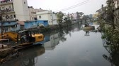 borough : India, kanniyakumari - January 26, 2016: Cleaning and deepening of old city canal, water stagnation, picture of stagnation and onset of nature, tropical city, excavator work. South Asia
