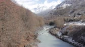 Beautiful spring landscape with river in gorge and snow-capped peaks. Mountain village, aul. Abkhazia. Caucasus