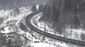 ton : freight train moving through coniferous forest during snowfall along frozen river among hills. Northern country. Side fron top Stok Video