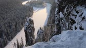 реликвия : Weathering pillars (circumdenudation mountain) on Siberian river. Beautiful winter panorama of frozen river and Northern fir forests. Stone outcrops in form of pillars with height of up to 20 meters