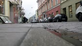 borough : Lithuania, Vilnius - September 5, 2017: Old street with a Church in the city center. The low position of the camera when shooting bystanders