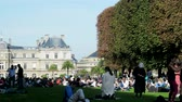 folk : Paris, France - 24.09.2017: huge number of Parisians resting on lawn on summer day. Overpopulation of megacities and craving for nature, average man Stock Footage