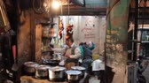 senior people : India, Himachal Pradesh- March 16, 2018: Indian street cafe. Fried chicken hung from the ceiling instead of the window, cook works in front of the client Stock Footage