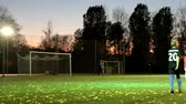 stopy : Russia, St. Petersburg-October 15, 2018: Night football. Teenagers training football competitions at soccer stadium with lighting, autumn sunset, the wind drives the fallen leaves. Youth football