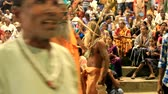India, Varanasi - March 20, 2018: Sacred holiday and the audience on the podium. In the foreground a naked sadhu (yogi) Stock mozgókép