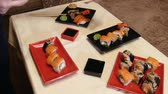 pauzinho : Cook puts plates with sushi at the table.Serving sushi in the red plate