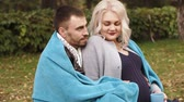 doğurganlık : HD Couple is sitting in a park husband is covering his pregnant wife with a blanket