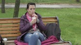 4K Women in jacket sits on the bench in the park and drink hot drink through the straw Wideo