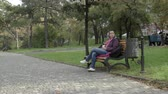 4K Woman is holding coffee and looking with estimation in the park on a bench. Stock Footage