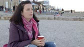 4K the beautiful lady in spring coat sits on the beach with cup of hot drink Wideo